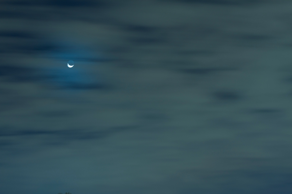 Crescent Moon in the night sky behind clouds