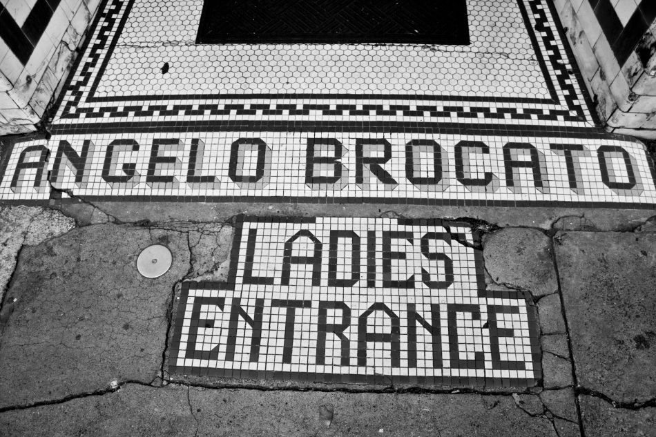 "An old mosaic sign outside the old location of the Angelo Brocato ice cream parlor embedded into the sidewalk in the French Quarter in New Orleans that reads ""Angelo Brocato Ladies Entrance"""