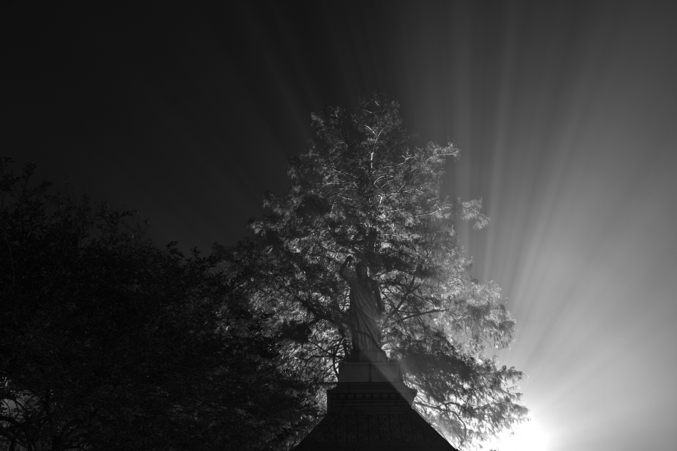 Rays of light emanating from behind a statue during a foggy night in New Orleans
