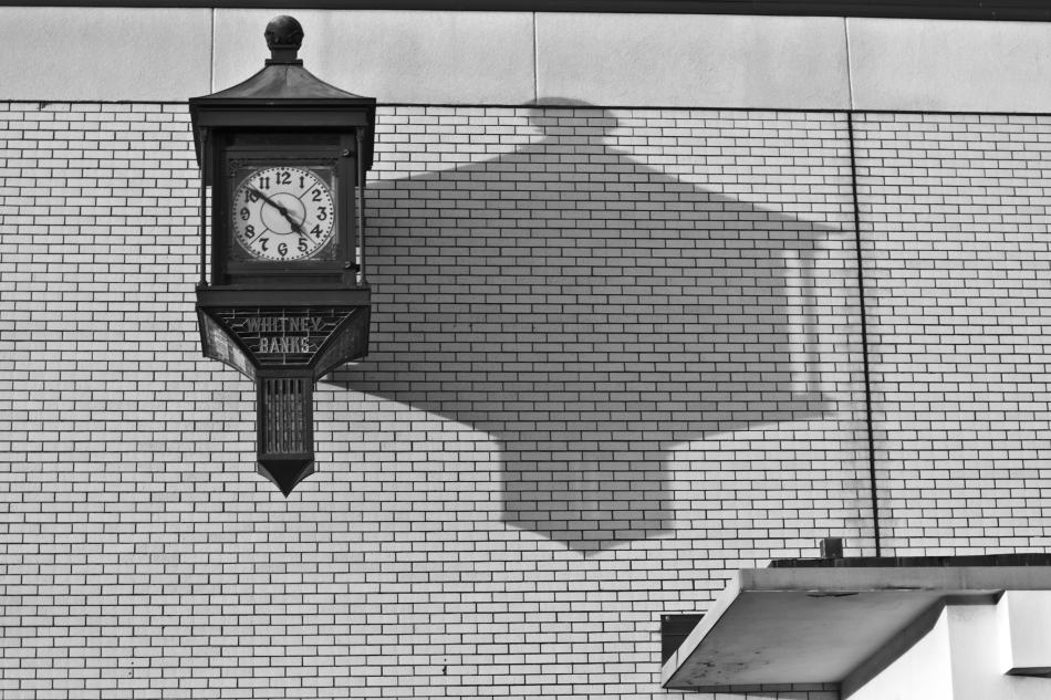 A clock reading 4:51 P.M.  protruding from a Whitney Bank on St. Claude Avenue casting a long shadow.