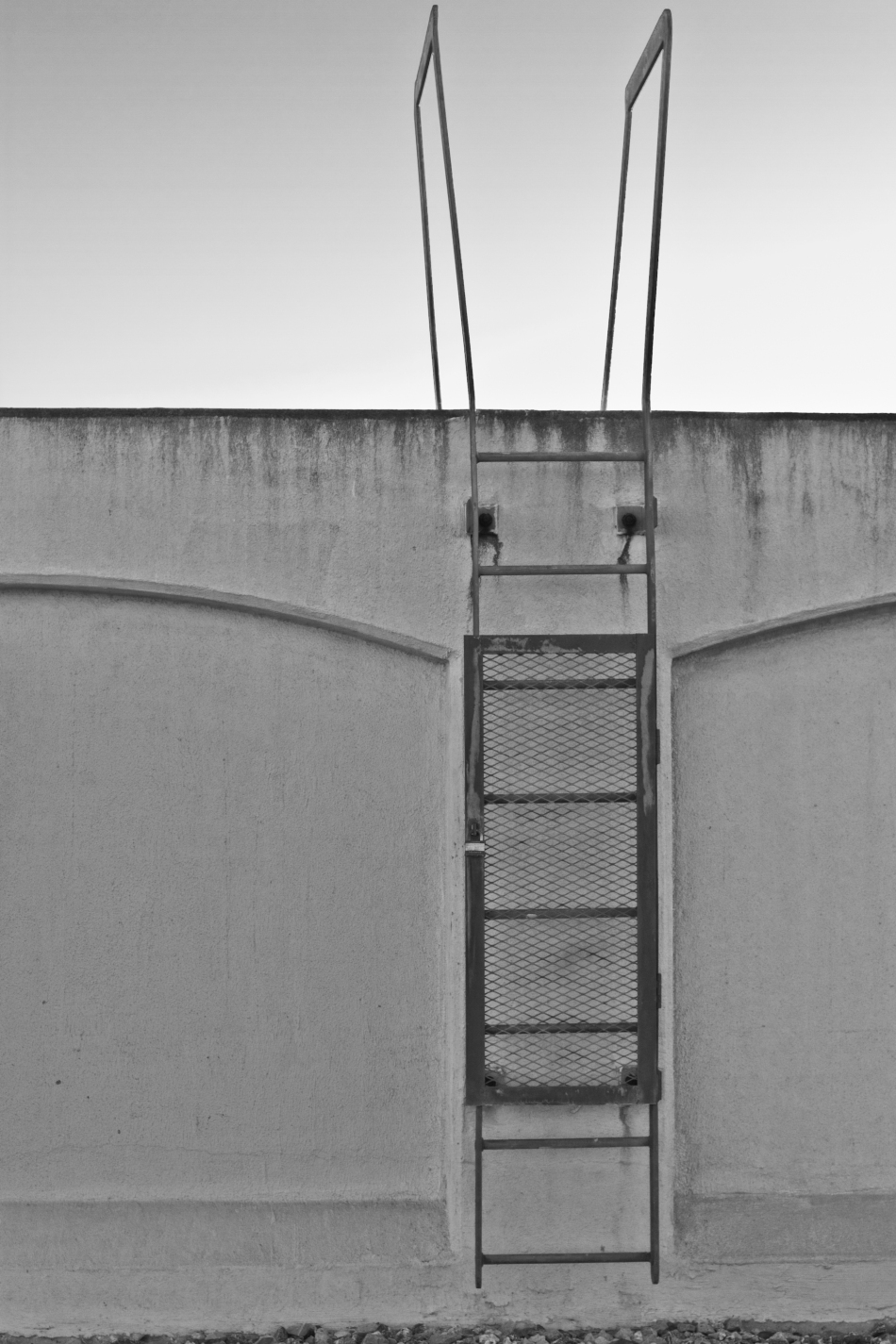 A ladder mounted on a wall running along the Mississippi River in the Bywater of New Orleans, LA