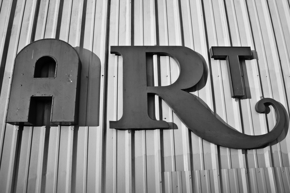 A large sign that reads ART hanging on a metal wall in the Bywater of New Orleans, LA