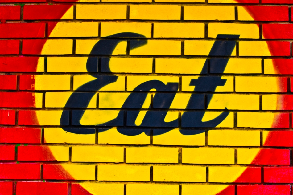 A sign painted on a brick wall reading Eat