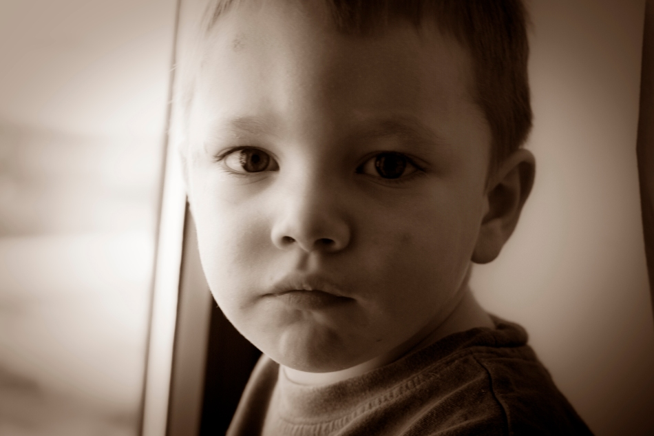A child looks directly at a camera making a serious face in sepia tone