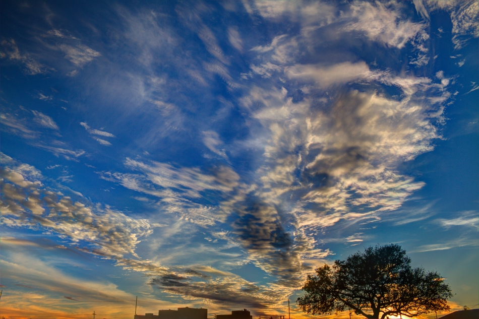 High Dynamic Range image of a sunset and clouds with the silhouettes of a tree and some buildings in the background.