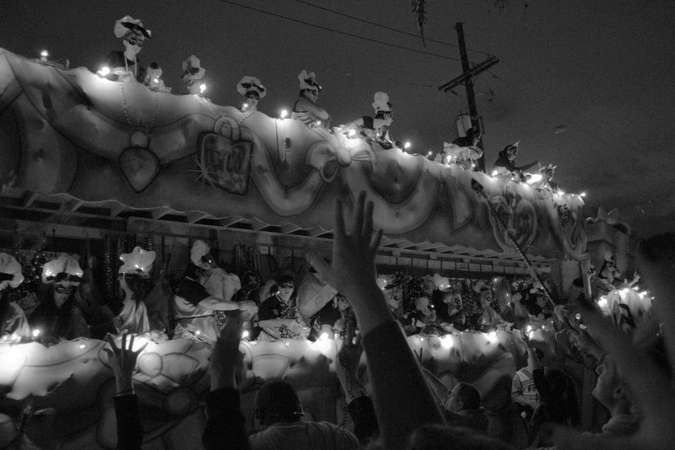 The Nyx Mardi Gras parade in Uptwn New Orleans, LA on February 6, 2013. Revelers reach for beads as a float passes by.