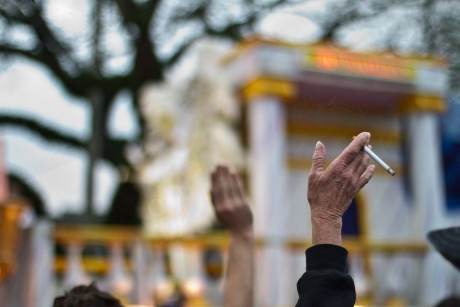 A parade-goer waves her hand while holding a cigarette at the Endymion Mardi Gras parade in New Orleans, LA on February 9, 2013