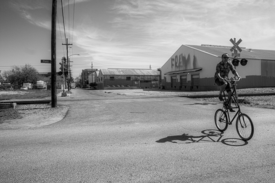 A man riding a tall bike through the Bywater Neighborhood of New Orleans