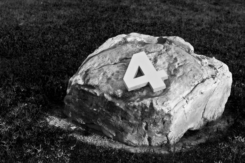 A number four on top of a rock.