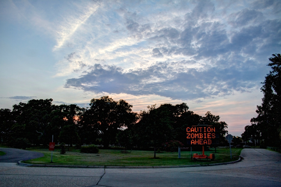 "A City Park evening scene with a traffic sign reading ""Caution Zombies Ahead"""