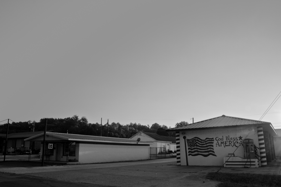 "A kodak film store and a gas station in Ellington, MO with a painting of an American flag that reads, ""God Bless America."""