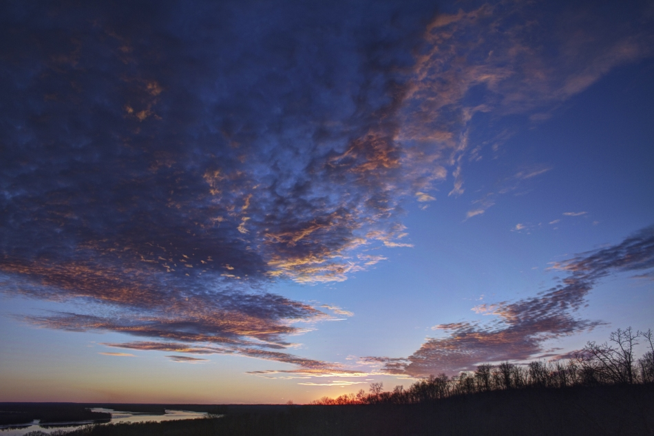 A high dynamic range image of the sunset on the horizon over the Illinois River in Grafton, Illinois.