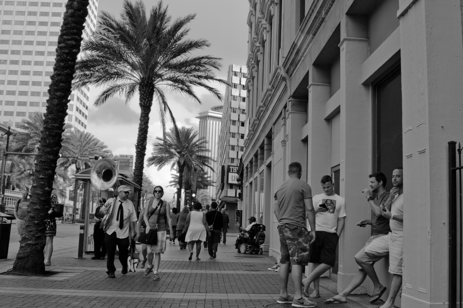 A black and white street photography image of people walking down Canal Street in New Orleans, LA