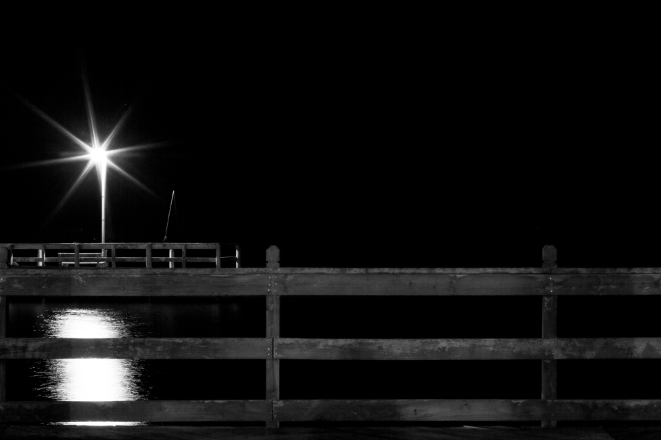A black & white night shot of a dock on the Gulf of Mexico at night. Photo by Braden Piper bgpiperphotography.com
