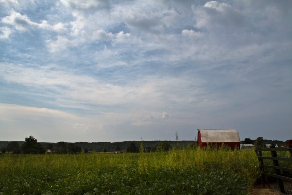 An image of a red barn standing in a field on some rural farmland with dynamic clouds.