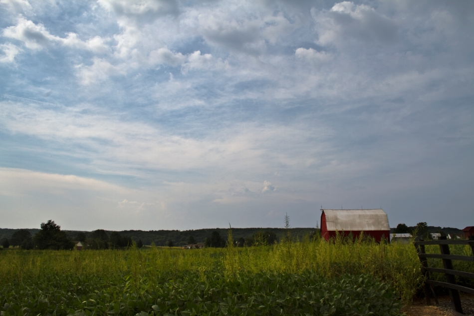 An image of a red barn standing in a field on some rural farmland in Bloomsdale, Missouri with dynamic clouds.