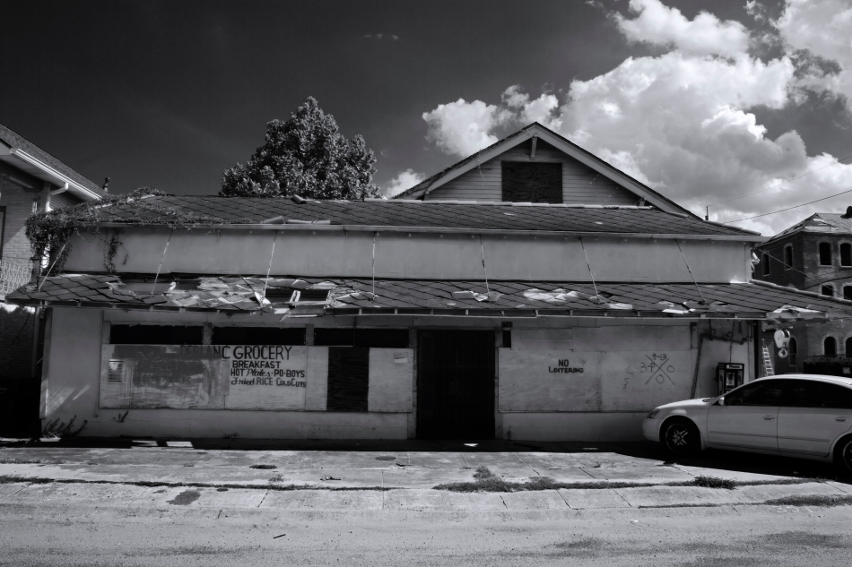 A black and white image of a dilapidated grocery store, Leblanc Grocery, in the Treme neighborhood of New Orleans, LA