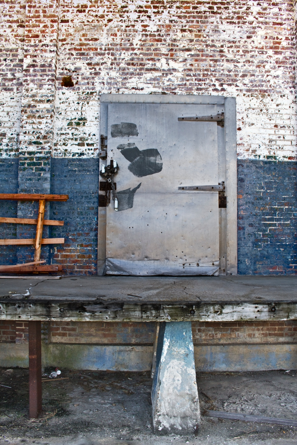 An image of am industrial metal door in a red brick wall partially painted blue