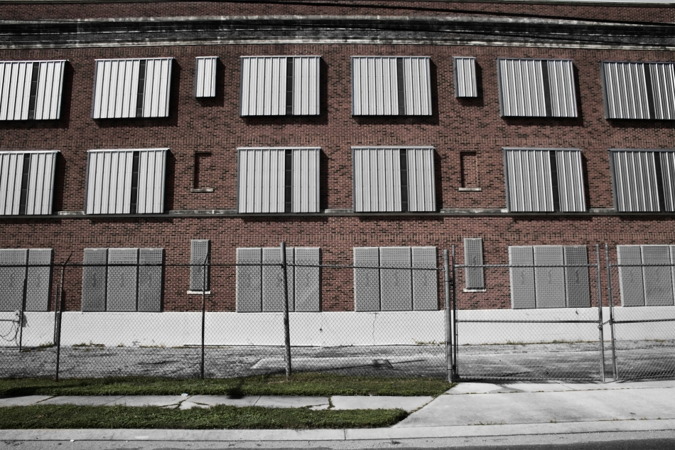 A partially black and white, partially color photo of a brick wall, behind a chainlink fence with some grass in the foreground in the 7th Ward of New Orleans, Louisiana.