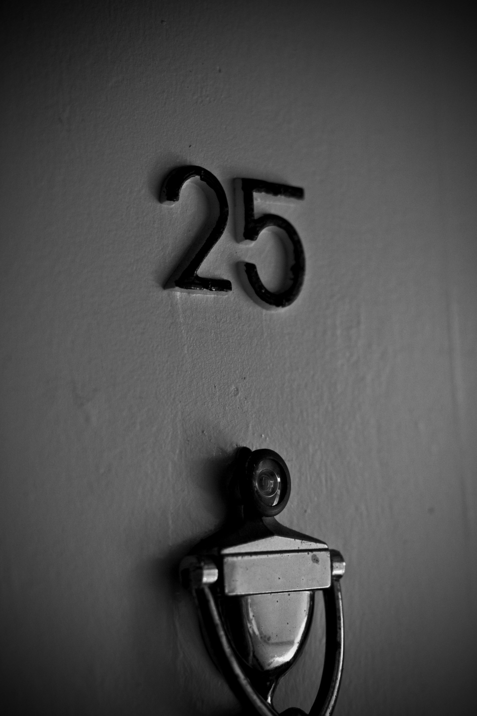 Address numbers reading 25 hung on a door with a door knocker and a peephole in black and white.