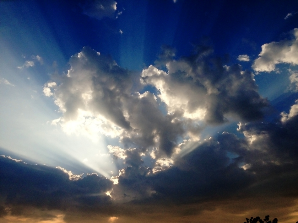 Beams of sunlight shining through clouds in a blue sky