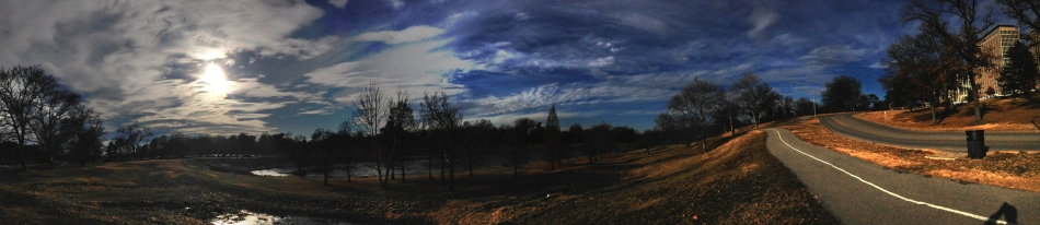 A panoramic shot of Forest Park in St. Louis, MO with clouds and a bike path