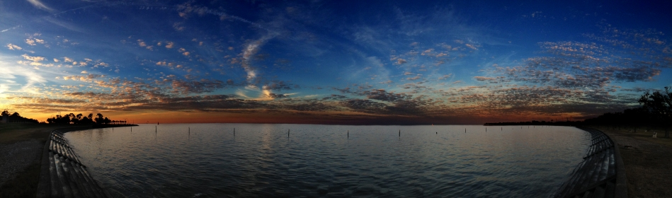A panoramic view of Lake Ponchartrain in New Orleans, LA shortly after sunset with clouds in the sky reflecting off the water